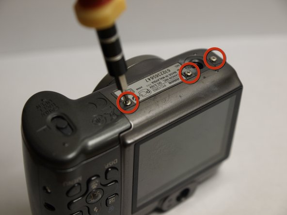 Remove the three screws located at the bottom of the camera using a magnetic screwdriver.