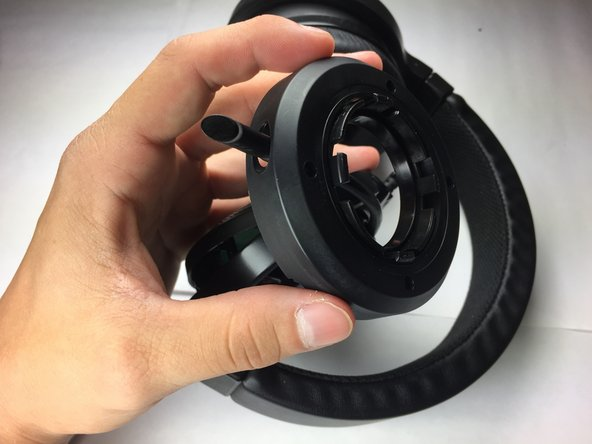 Slide the speaker case laterally along the length of the microphone until the casing is completely detached from the headset.