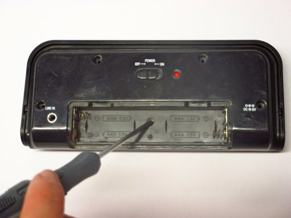 Image 2/2: Push down gently on the battery case cover and slide it in the direction the arrows indicate. Remove the batteries.