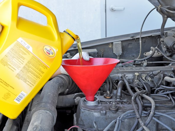 Pour 4 quarts of oil into the engine. Use one hand to stabilize the funnel to help prevent spills. We chose 10W-30 engine oil for this oil change.