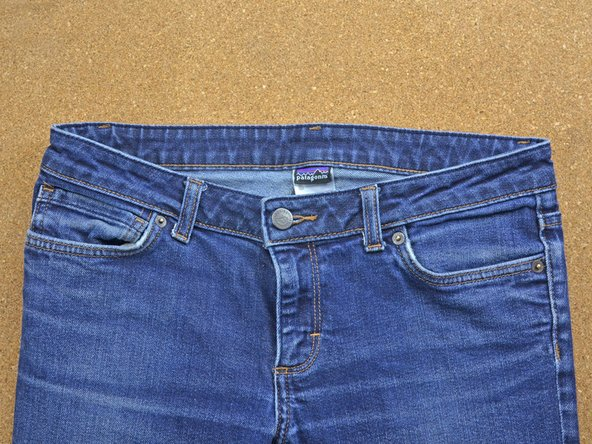 Test out your new button by buttoning the jeans to ensure the new button is set and secure.