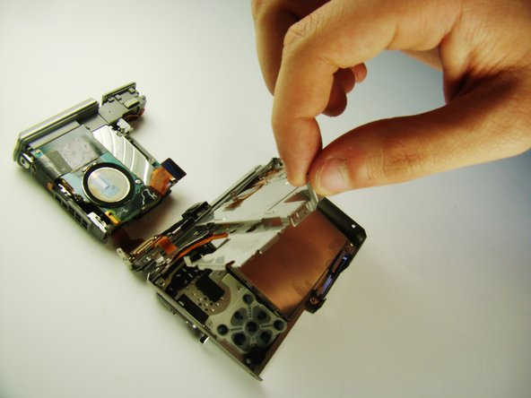 Lift and remove the metal plate covering the LCD screen from the camera.
