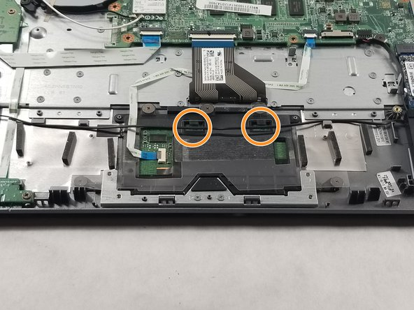 Remove the black wire running across the touchpad from the two hooks on top of the part.