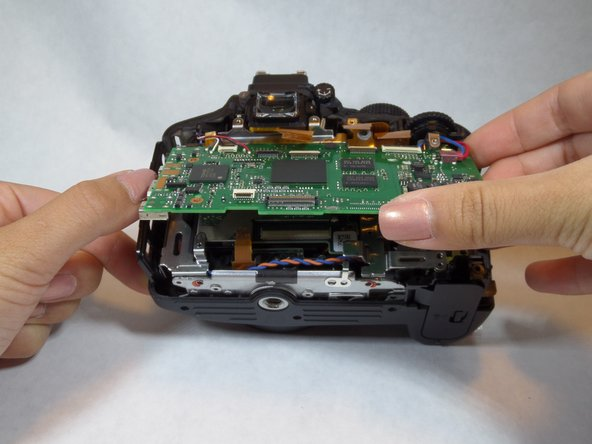 Image 3/3: Carefully lift the motherboard from the camera and you're set!