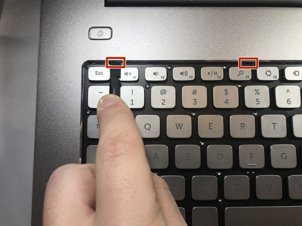 Using the plastic spudger tool, place the tip of the spudger into the small notches at the top of the keyboard and  push in the notch to release the top portion of the keyboard. Repeat on all notches.