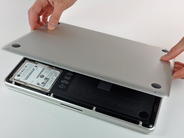 Image 1/1: Slightly lift the lower case and push it toward the rear of the computer to free the mounting tabs.
