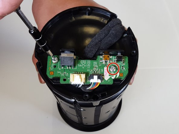 Image 1/2: With caution remove the Port Panel from the speaker body, exposing the ribbon cables.