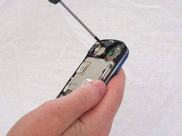 Retirez délicatement les deux vis Phillips #00 3mm (une en haut et une en bas) qui fixent la carte mère au téléphone.