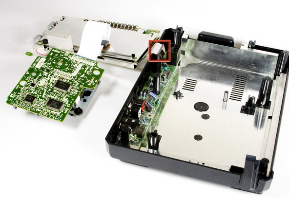 Carefully lift off the metal plate, the motherboard, and the CD tray circuit board and flip each piece over, as pictured.
