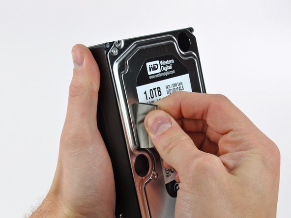 Image 1/1: Carefully peel off the piece of EMI foam attached to the front of the hard drive.