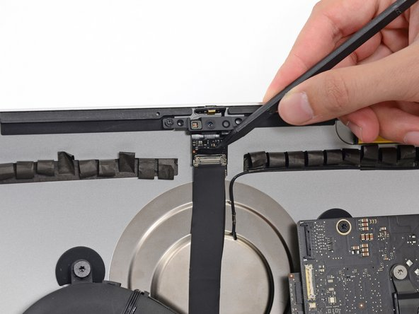 スパッジャーの先端を使って、カメラケーブル上のメタル製の固定ブラケットを裏返します。