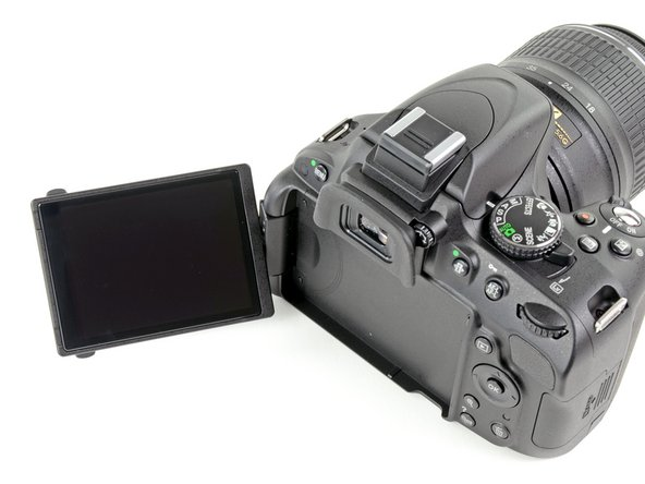Image 1/2: Unlike the D90, the top of the camera does not include an informational LCD. Instead, we get the rotating mode selector on the right.