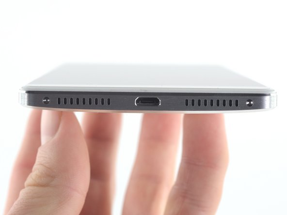 Image 1/3: Once the screws are removed, the display assembly is freed from the phone case by disengaging the clips on the perimeter of the phone.