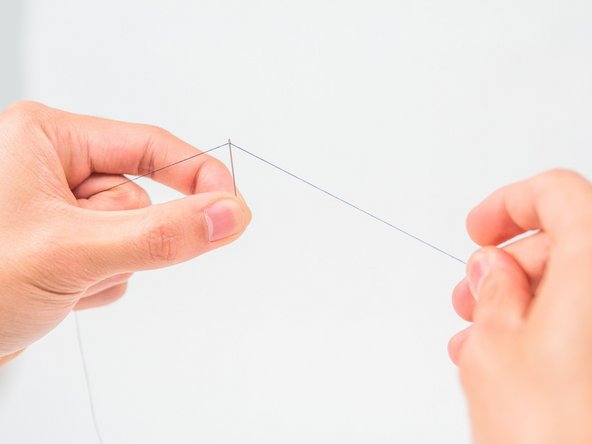 Pull the thread through the eye of the needle until it is about a hand's length.
