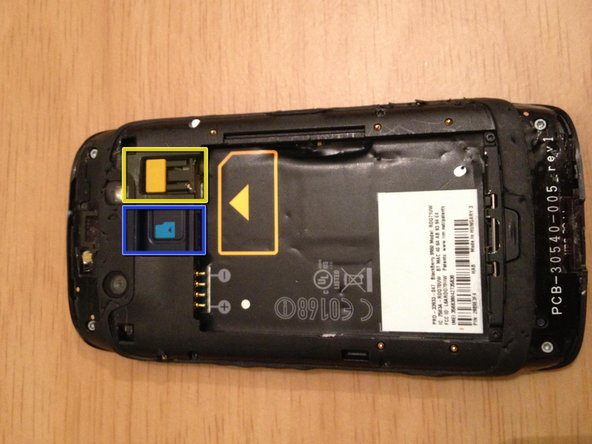 Image 2/2: Slide the yellow button toward the battery to eject the SIM card
