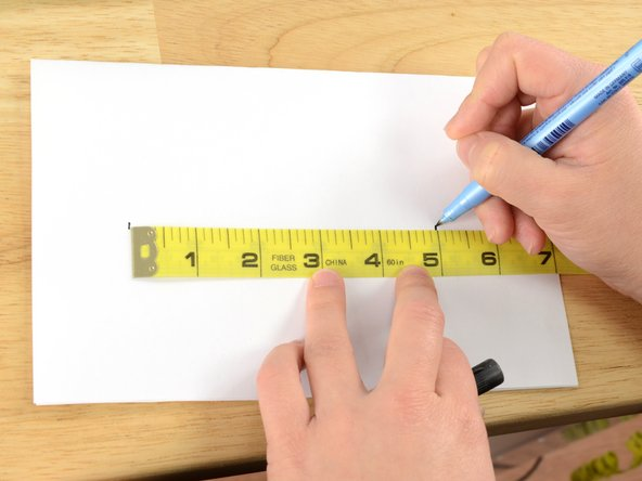 On a piece of paper, mark the endpoints of a line that measures the length of the hole, plus one inch.