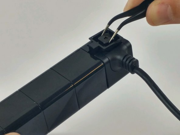 Using tweezers, remove the cap holding the cable grommet in place.