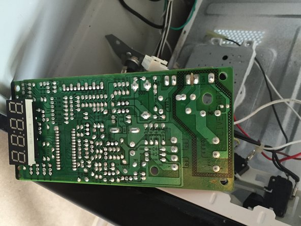The PCB for the keyboard and the LED display has two phillips screws hidden between on-board components. The board also has several connectors that cannot be removed reliably without jeopardizing the functionality of the oven, so it is recommended to leave the board connected unless it must be replaced.