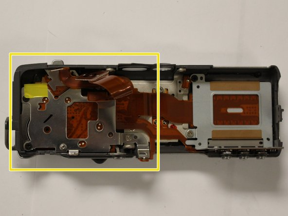 With the top panel removed, locate the metal plate covering the zoom control on the underside of the panel (located on the forward left side, if the panel is oriented similarly to the first image.) This plate will also be connected to some circuit ribbon. Leave the ribbon attached to the plate.
