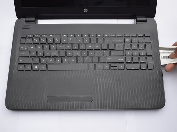 Turn the computer over and use a card to pry the space between the keyboard and bottom surface of the computer.