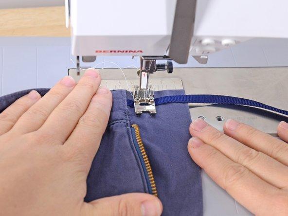 Cucire la fettuccia sul capo di abbigliamento.