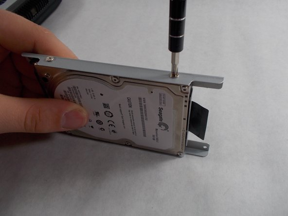 Using a Phillips #0 screwdriver, remove the cage screws on the side of the hard drive.