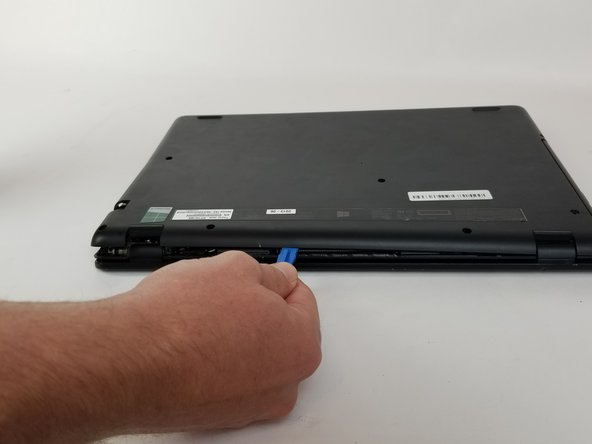 Insert the plastic opening tool into the slit between the back cover and the rest of the computer.