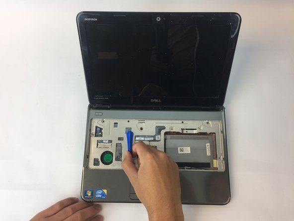 Start by prying the outer casing of the laptop using the plastic opening tool. Start from the bottom and work your way around the edges.