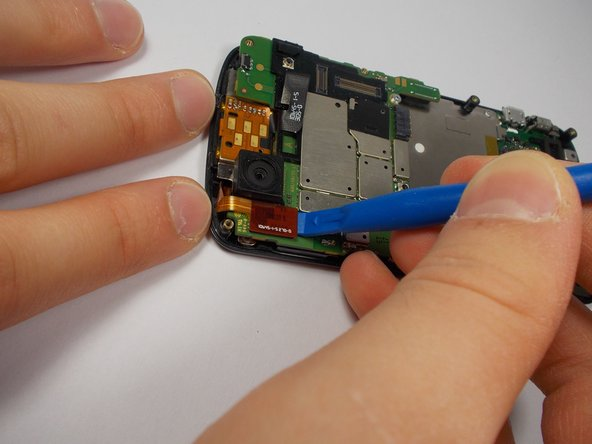Use your plastic opening tool to disconnect the two ribbon cables at the top of the phone.
