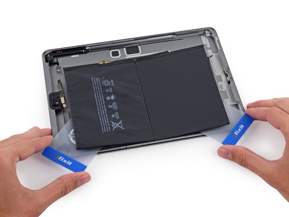 Grip both cards firmly and twist them to lift the battery off of the rear case.