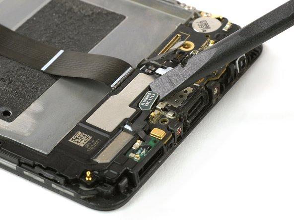 Avec une spatule, déconnectez de la carte fille la nappe du haut-parleur et celle du port de charge.