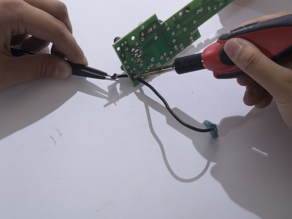 While maintaining contact with the solder iron, free the wire end by pulling the wire away from the board with the tweezers.