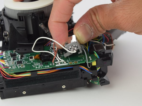 Remove the flash bulb from the circuit board by shifting it towards the side with the motor and lifting.