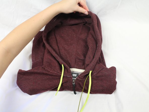Remove the wire from the hoodie by pushing the left end of the wire through the hoodie, while pulling the right end out.