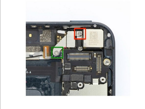 Starting at the top of the phone, remove the two Phillips screws holding the camera flash retaining plate.