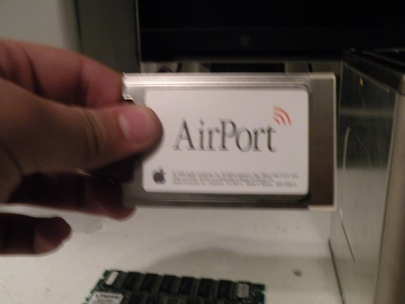 Flip the cube to the side with the airport card attatched.  Remove the antenna cable, then grasp the card by the plastic tab, and pull it out of it's socket.