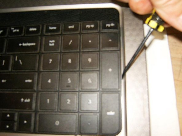 Image 2/2: Do not use anything to pry on the bottom of the keyboard. This is where solid plastic tabs are located; those may break off. The keyboard needs to be tilted to the bottom to remove it