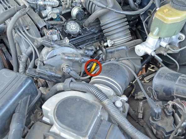 Locate the yellow oil dipstick next to the driver's side valve cover and the distributor cap.