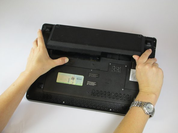 Image 2/3: Remove the battery unit from the laptop and set it aside.