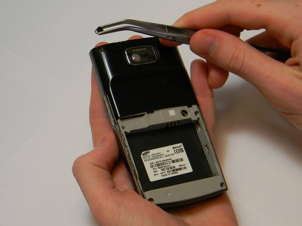 To get a better grip, you may use the tweezers to finish pulling the plastic caps from the phone.