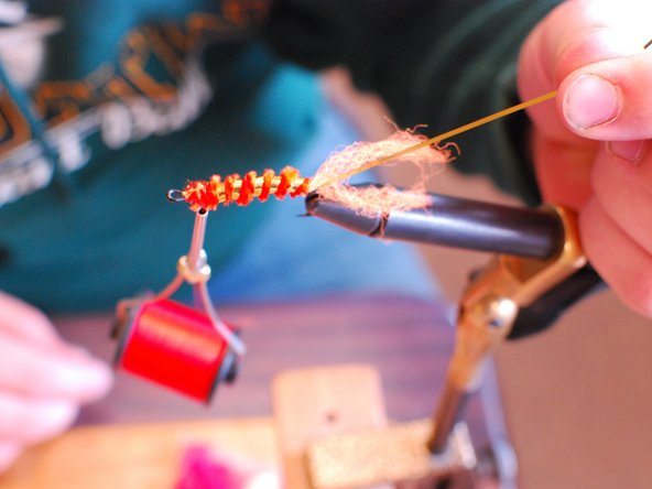 Image 2/2: Take the tinsel and wrap it around the body in a spiral and tie it off at the end of the hook and leave the tail as long as you want.