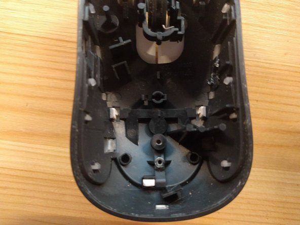 The top mouse cover can be removed by undoing three white clips holding it on the grey plastic part.