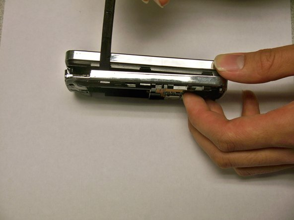 Insert a spudger or plastic opening tool into the seam on the side of the phone.