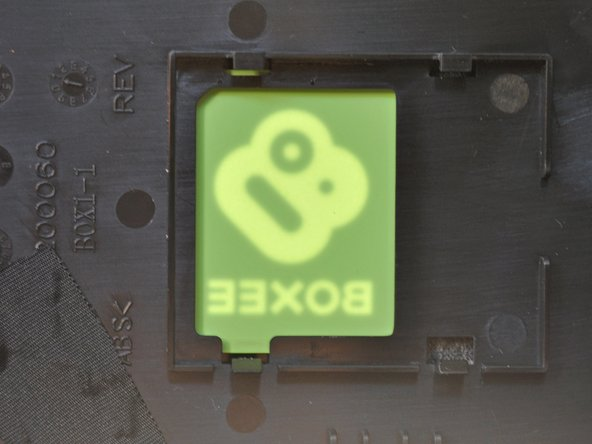 Image 3/3: A soft white plate on the status panel disperses the light from a couple LEDs to illuminate the semi-transparent Boxee logo either orange (standby) or green (running).