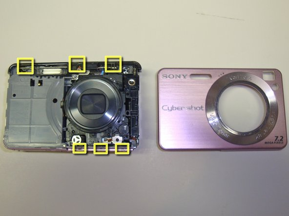 Image 3/3: Once the tabs have been released, the front bezel will simply lift off the camera.  The approximate locations of the tabs are indicated by the yellow boxes.