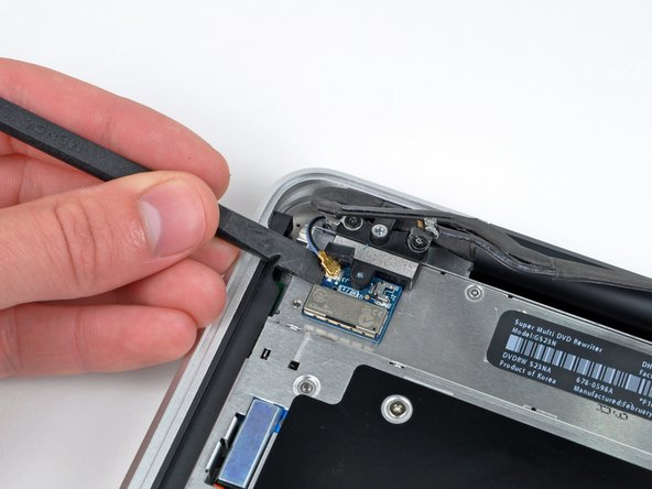 Use the flat end of a spudger to carefully pry the AirPort antenna off its socket on the AirPort card.