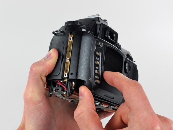 Image 2/2: Carefully pull the sides of the rear cover away from the body of the D70.