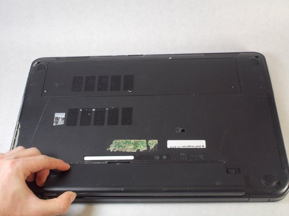 Use your thumb to lift the battery out of its slot by lifting the bottom edge of the battery.