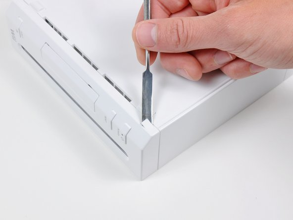 Use a metal spudger to remove the white plastic screw covers stuck to the lower case near the front of the Wii.