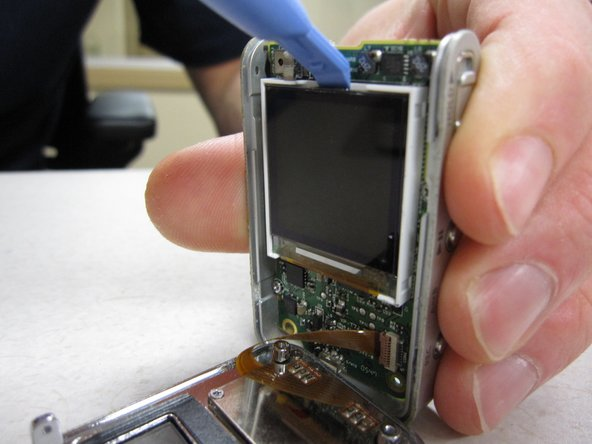 Place the pry tool between the LCD screen and the white housing unit